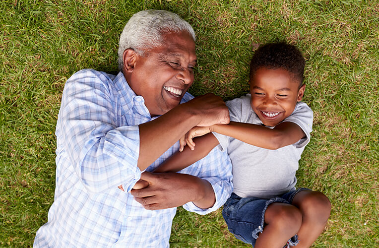 Health and Wellness - Grandfather and grandson play lying on grass aerial view